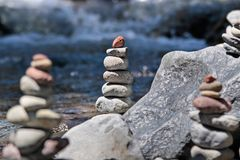 Cairn by the stream. Cairn with red stone by the stream in the Tongariro National Park, Manawatu-Wanganui, New Zealand stock image