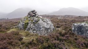 Cairn surrounded by heather with hazy hills behind. On Lingmell above Ennerdale looking to a hazy Long Crag with Pillar to the left, widescreen royalty free stock images