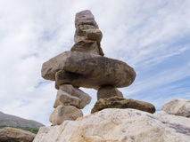 Cairn trail marker Inuksuk large stacked stones. Large rocks stacked and balanced to form an Inuksuk stone landmark or cairn as a marker or monument in Royalty Free Stock Image