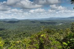 Wide look over Kuranda Rain Forest, Cairns Australia. Cairns, Australia - February 18, 2019: Wide view over green Kuranda green Rain Forest with its hills. Blue royalty free stock photos