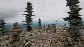 Cairns piled up on top of mountain summit. Camera slowly moving between cairns, human-made pile or stack of stones on top of mountain, natural landmarks for stock footage