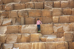 Cairo, EGYPT - Apr 22, 2015, The girl sitting on the ancient stones of the Egyptian pyramids at Giza, on Apr 22 2015 in Cairo, EGY Stock Photo