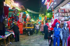 CAIRO, EGYPT - DECEMBER 21, 2017: The busy narrow Al Muizz street with garment stalls, walking people and driving tuk tuks, on royalty free stock photography