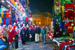 CAIRO, EGYPT - DECEMBER 21, 2017: The crowded narrow Al Muizz street, lined with market stalls, with a view on medieval brightly royalty free stock photography