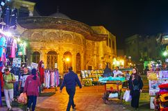 CAIRO, EGYPT - DECEMBER 21, 2017: The evening shopping in Al Muizz street of busy market, the medieval sabil-kuttab of Tusun Pasha royalty free stock photography