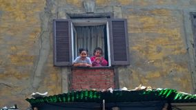 Two little girls at the window in Cairo. CAIRO, EGYPT - DECEMBER 21, 2017: Two little girls play at the window, watching passers by and loughing, Al Muizz street stock video