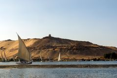 Cairo, Egypt February 17, 2017: Turku Nile River boats called felucca loaded with tourists passing under a huge desert dune with t. He tomb of the Aga-Khan on Stock Photos