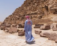 CAIRO, EGYPT - MAY 22, 2017: Arab man with camel near pyramid. In Giza stock image