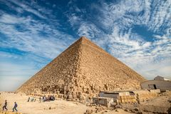 View of the incredibly majestic pyramid of the cheops on a sunny day in the desert with a road royalty free stock photo