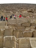 Cairo . Giza valley/ Egypt-January 05 2008: tourists are claiming on the Pyramid. Big stones are on the foreground Royalty Free Stock Image