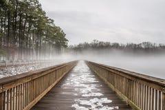 Cais atarracado da pesca de lago na neve, no gelo e na névoa fotos de stock royalty free