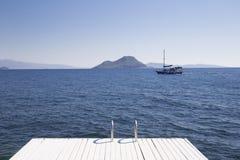 Cais branco no primeiro plano e um veleiro que flutua no mar Imagens de Stock
