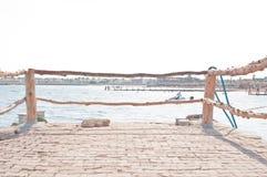 Cais com uma cerca azul brilhante na perspectiva Farol vermelho grande no Lago Michigan Cercas azuis brilhantes no cais fotos de stock royalty free