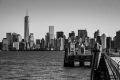 Cais da aterrissagem em Liberty Island na frente da skyline Blac de New York imagem de stock