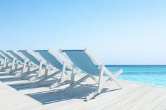 Cais de madeira com uma fileira de cadeiras de plataforma azuis Fotografia de Stock