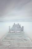 Cais de madeira no lago em um modo nebuloso e nevoento. foto de stock