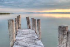 Cais de madeira no lago no por do sol Foto de Stock