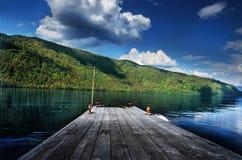 Cais de madeira pequeno para barcos em um lago com um Mountain View Foto de Stock Royalty Free