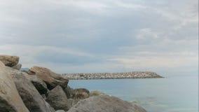 Cais de pedra no mar Os povos andam ao longo dele rapidamente, nuvens flutuam Timelapse vídeos de arquivo