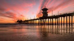 Cais do Huntington Beach durante um por do sol vermelho e alaranjado imagem de stock