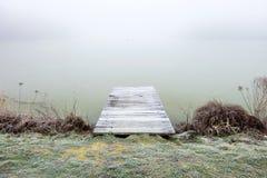 Cais em um lago nevoento Imagem de Stock Royalty Free