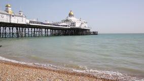 Cais inglês tradicional de Eastbourne com praia e ondas video estoque