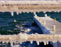 Cais no gelo com a cerca congelada defocused fotografia de stock royalty free