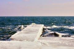 Cais no gelo pesado e em sincelos longos na pedra na água foto de stock royalty free