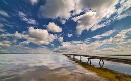 Cais no grande lago sob o céu azul e as nuvens Fotografia de Stock Royalty Free