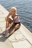 Cais novo da água dos pés do estiramento da mulher do esporte Fotografia de Stock