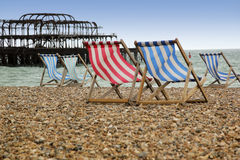 Cais ocidental dos deckchairs da praia de Brigghton fotografia de stock royalty free