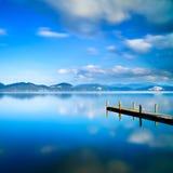 Cais ou molhe de madeira e em uma reflexão azul do por do sol e do céu do lago na água. Versilia Toscânia, Itália Fotografia de Stock