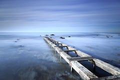 Cais ou molhe de madeira em um oceano azul na manhã Exposur longo fotografia de stock royalty free