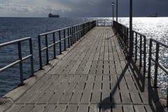 Cais que estica no mar e nos navios no horizonte Imagem de Stock