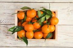 Caisse avec les mandarines mûres fraîches sur le fond en bois photographie stock libre de droits