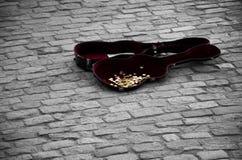 Caisse de guitare complètement de pièces de monnaie sur les tuiles grises Image libre de droits