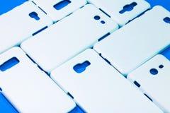 Caisses blanches de téléphone sur le fond bleu vif Points de droit ou protecteur mobiles de smartphone pour votre conception photographie stock