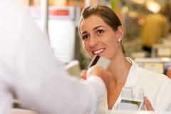 Caissier dans la prise de supermarché par la carte de crédit Images libres de droits