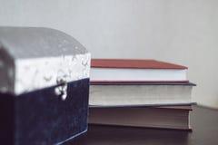 Caixão e livros grandes em uma tabela de madeira Fotos de Stock Royalty Free