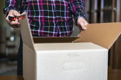 Caixa aberta da mão ascendente próxima com coisas ao mover-se para a casa nova f da casa fotos de stock