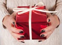 Caixa atual do vermelho com curva nas mãos das mulheres com prego e a camiseta pretos fotos de stock royalty free
