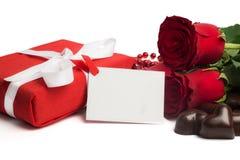 Caixa atual do vermelho com fita, as rosas vermelhas, o cartão e os doces Fotografia de Stock