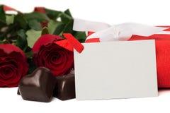 Caixa atual do vermelho com fita, as rosas vermelhas, o cartão e os doces Fotos de Stock
