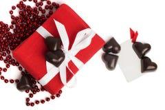 Caixa atual do vermelho com fita branca e doces no branco Imagens de Stock