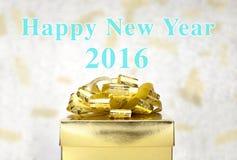 Caixa atual dourada com palavra do ano novo feliz 2016 na luz do bokeh Fotografia de Stock Royalty Free