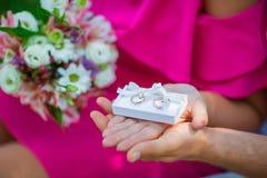 Caixa branca do casamento com alianças de casamento do ouro nas mãos das noivas em um vestido cor-de-rosa com um ramalhete das fl Imagem de Stock Royalty Free