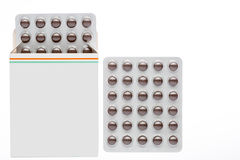 Caixa cinzenta com comprimidos marrons em um bloco de bolha foto de stock royalty free