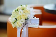 Caixa com alianças de casamento do ouro e um ramalhete das rosas brancas Imagens de Stock