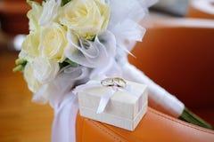 Caixa com alianças de casamento do ouro e um ramalhete das rosas brancas Imagem de Stock
