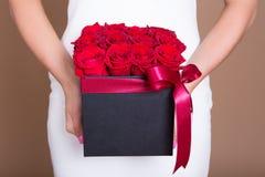 Caixa com as rosas vermelhas nas mãos fêmeas imagem de stock